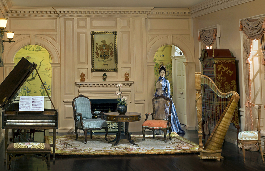 I bought this room box by William Bowen which included the John Hodgson pie plate table, piano by Glenn Partelow, and chinoiserie cabinet which is signed, but I cannot read the signature. The wallpaper is a perfect choice to peer through the doorway. The double settee in the hallway was petit-pointed by Annelle Ferguson and the hall rug is by Pat Hartman.